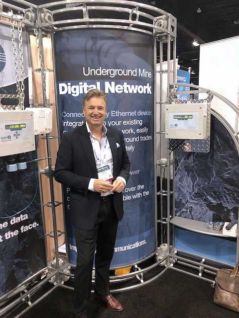 Mike Gribbons standing in front of the Maestro Digital Mine booth at the SME Conference