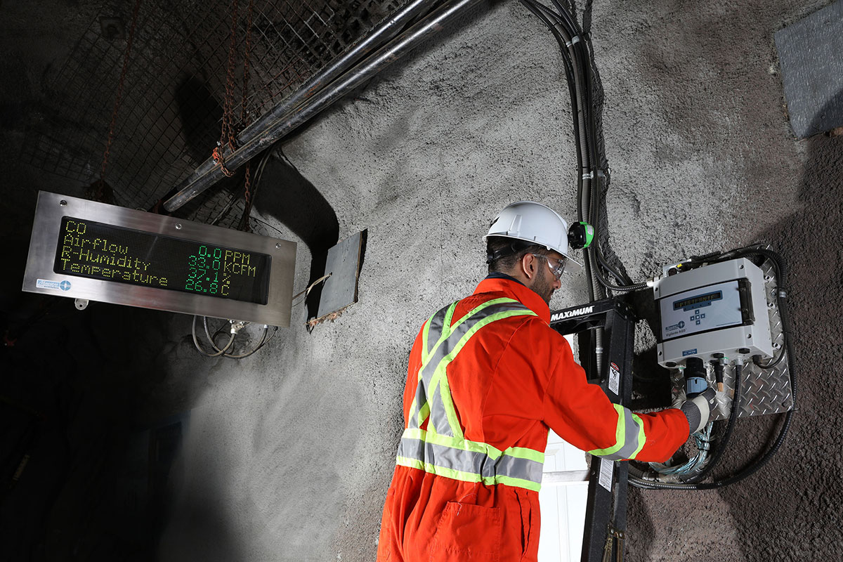 Miner in an underground tunnel, attaching the Maestro Digital Mine Vigilante AQS to their system. A Superbrite Display unit is in the background hanging from the tunnel roof.